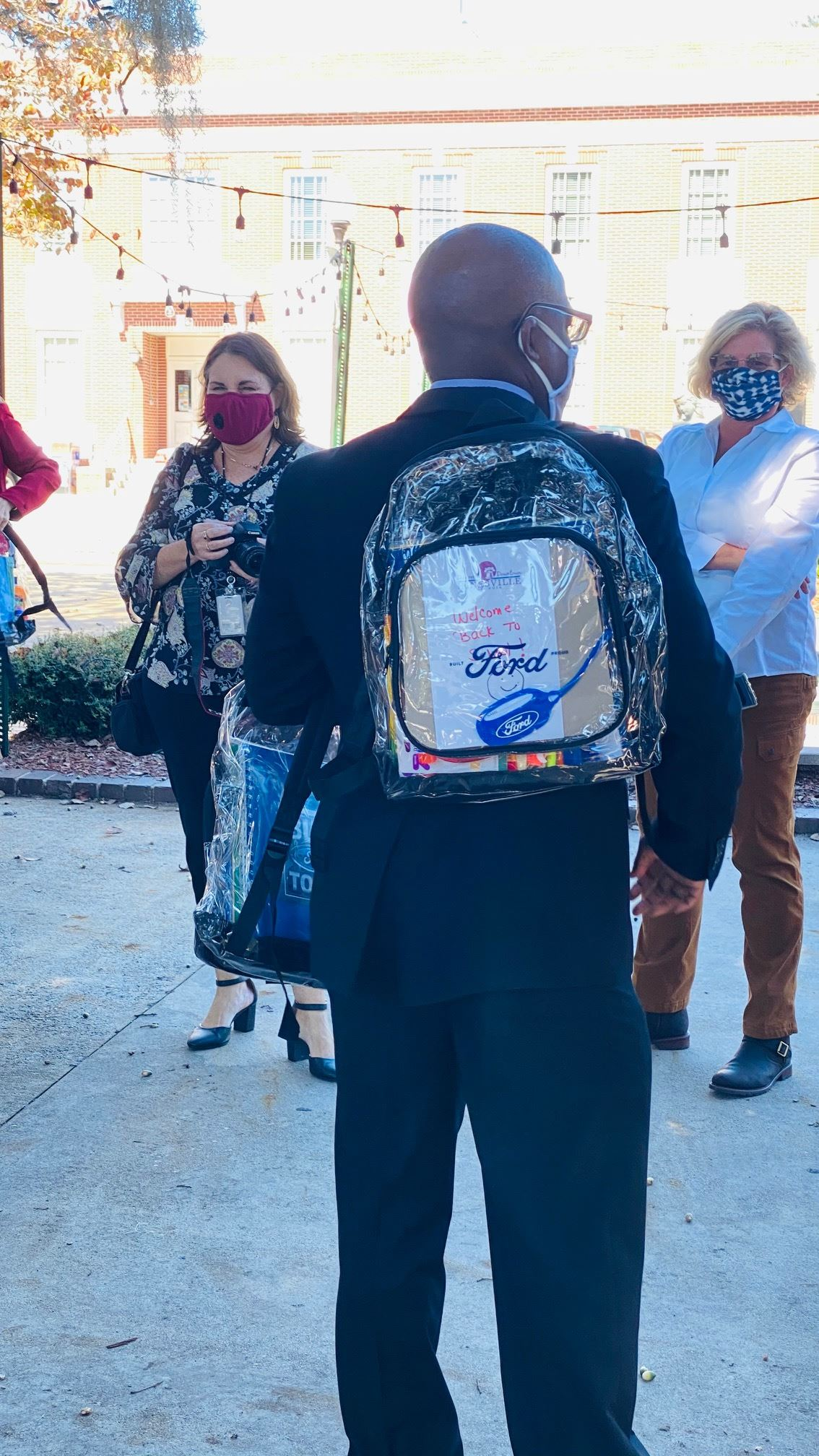 Hinesville District 5 Councilman Karl Riles wears carries a backpack to be given to a student